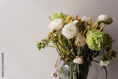 Photo  Close up of wilting green and white ranunculus and carnations in glass vase (sel