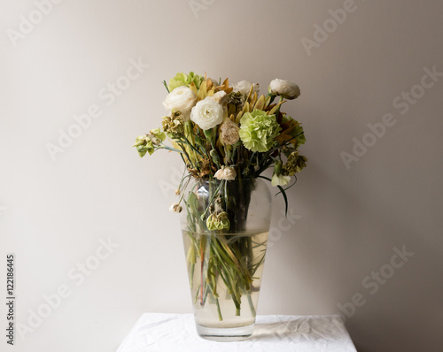 Fotografía  Wilting green and white ranunculus and carnations in large glass vase on small w