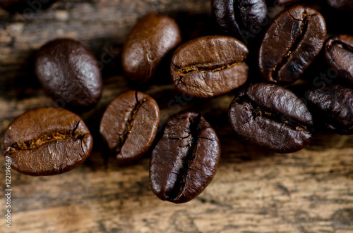 Close up arabica and robusta coffee beans roasted on wood background Canvas Print