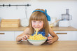 Portrait of a little girl in a blue dress funny eats a spaghetti from a dish and smiling
