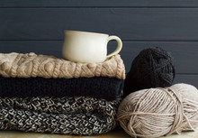 Stack Of Warm Clothes From Knitted Knitwear With A Cup Of Coffee