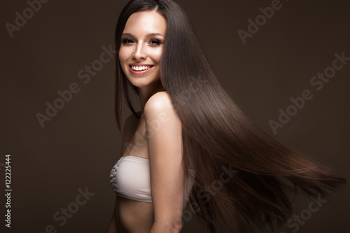 Obraz na plátně  Beautiful brunette girl in move with a perfectly smooth hair, and classic make-up