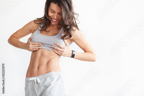 Fotografie, Obraz  fit woman showing her abs on white with copyspace