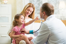 Male Pediatrician Examining Cute Little Girl With Stethoscope. Kid Happily Smiling And Pointing On Doctor. Mother Holding Her Kid. Doctor Visit His Patient At Home.