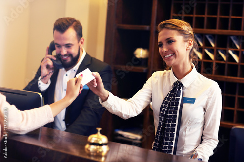 Guests getting key card in hotel Fotobehang