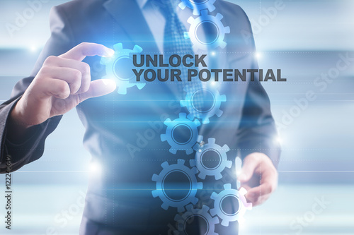 "Fotografía  Businessman is selecting ""Unlock your potential"" on the virtual screen"