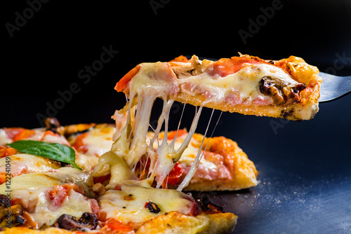 Fotografie, Obraz  cut off a slice of pizza. melted cheese stretches from the piece