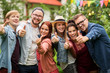 canvas print picture - happy friends showing thumbs up at summer garden