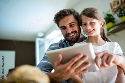 Obraz Father and daughter using digital tablet in the living room - fototapety do salonu