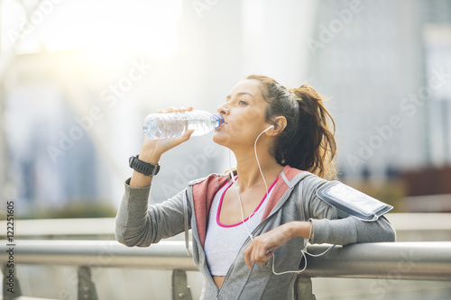 Fotomural Woman runner is having a break and drinking water