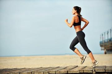 Žena trči na šetalištu plaže Santa Monica