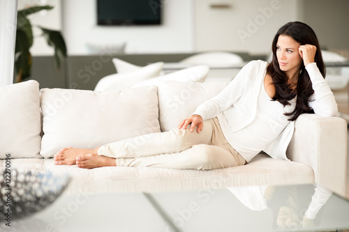 Fotografie, Obraz  Young Woman Lounging in Living Room on Couch