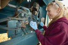 A Woman Working On Heavy Equipment On A Farm, Three Hills, Alberta, Canada