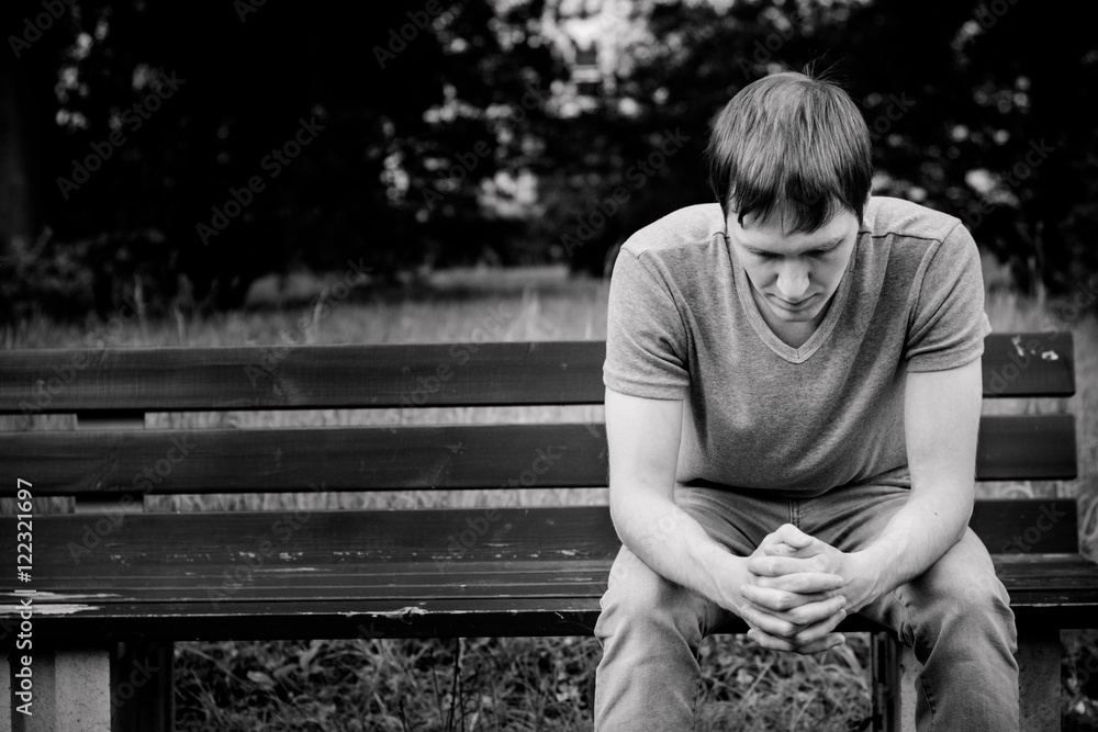 Fototapety, obrazy: A man sits on a bench. He is sad and pensive.