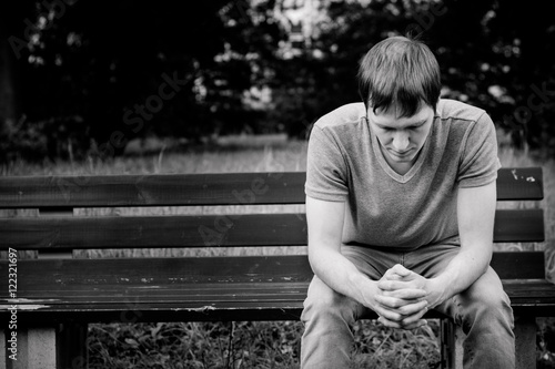 A man sits on a bench. He is sad and pensive.