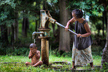 The Old Woman Pumping A Water Pump To Bathe Small Children.