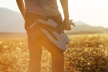 Closeup Photo Of Man With Guitar On Sunset Backdrop