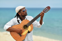 Afro-american Young Handsome Man In Sunglasses And Hat Is Playing Guitar On The Beach Of Caribbean Sea. Sound Of Atlantic Ocean And Cuban Guitar Music. Musician Is Singing Romantic Latino Song.
