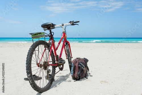 Foto op Plexiglas Bicycle is perked on the coast of Caribbean Sea with snow-white sand. Backpack and slates lie nearby.