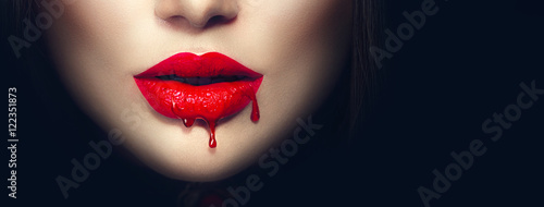 Sexy vampire red lips with dripping blood closeup isolated on black background Fotobehang