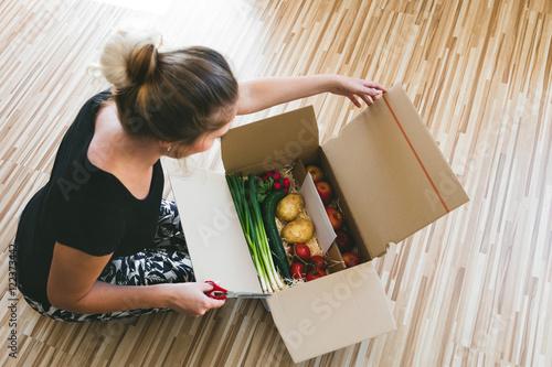 Fotografie, Obraz  Frau öffnet Kiste mit Lebensmitteln, Lieferservice per postsend