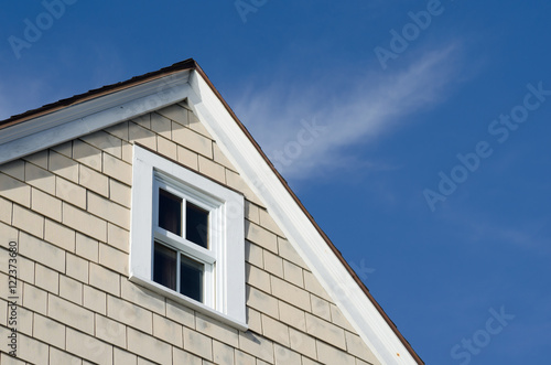 Obraz na plátne House peak with tan wooden siding and a white wood frame window against a beautiful blue sky