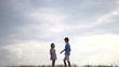 Boy Giving a Flower to Fashionable Girl on a Background of Clouds. Love Concept