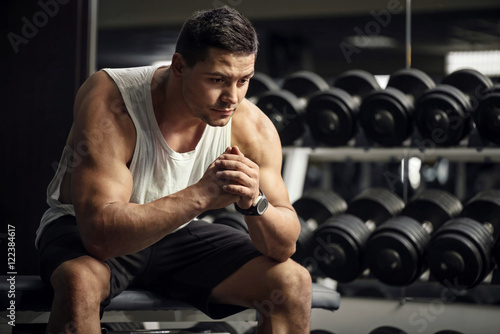 Thoughtful serious sportsman sitting in a gym Принти на полотні