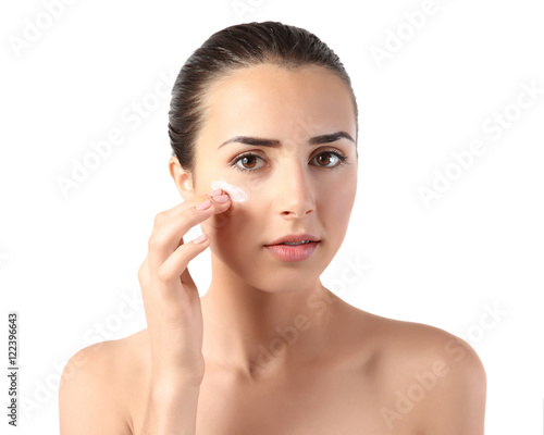 Fototapety, obrazy: Young woman applying facial cream on white background