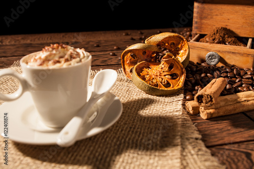 Spoed Foto op Canvas koffiebar Close-up of coffee cup, dried orange fruit and cinnamon sticks