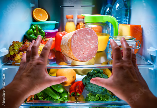 Fotografía  Human hands reaching for food at night in the open refrigerator