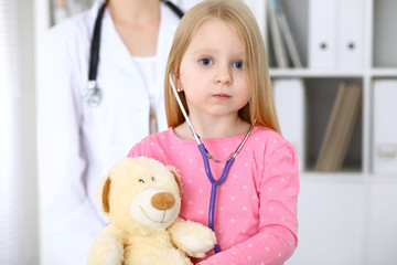 Little girl examining her Teddy bear by stethoscope. Health care, child-patient trust concept.