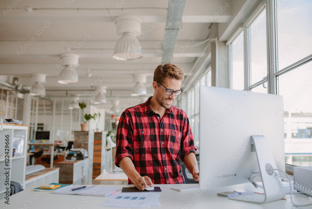 Fototapeta Young man working in modern workplace