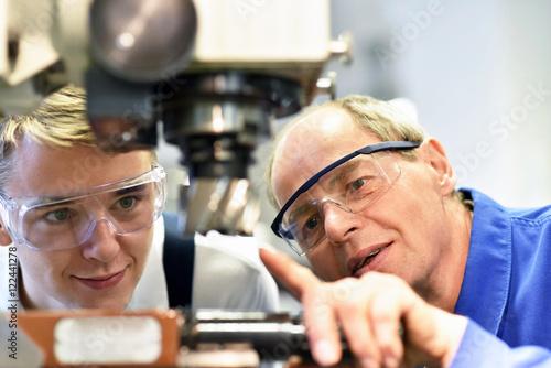 Foto  Berufsausbildung im Handwerk: Jugendlicher und Lehrer an einer CNC Maschine