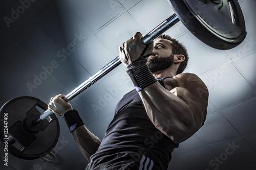 Hombre con grandes músculos levantando peso mientras entrena en el gimnasio. Ponerse en forma.