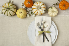 Fall Autumn Festive Table Setting Place Setting With Pumpkins, Plate, Fork, Knife And Napkin On Burlap Background