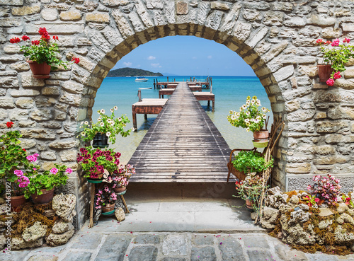 Seaview through the stone arch with flowers Canvas Print