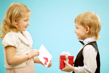Two Children Standing And Exchanging Presents, Gift For Girl And Post Card For Boy