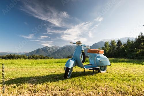 In de dag Scooter Blaue Vespa vor Bergkulisse auf Feld
