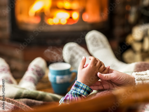 Warming and relaxing near fireplace. Mother and daughter holding