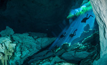 Divers Descending Into The Waters Of A Cenote On The West Coast Of Mexico's Yucatan Peninsula