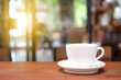 White coffee cup on wooden table with blurred cafe background.