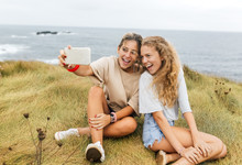 Two Screaming Teenage Girls Taking Selfie At The Coast