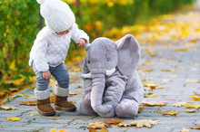 The Baby Girl And Toy Elephant Are In The Autumn City Park.