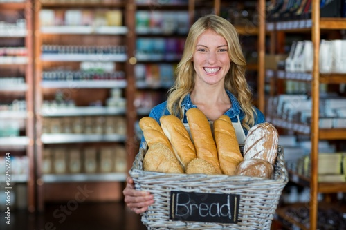 Autocollant pour porte Boulangerie Smiling female staff holding a basket of breads