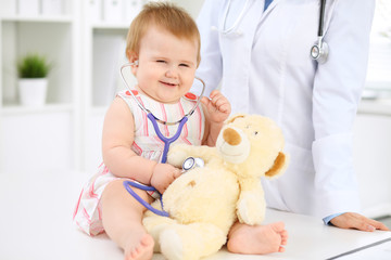 Happy cute baby  at health exam at doctor's office. Toddler girl is sitting and keeping stethoscope and teddy bear