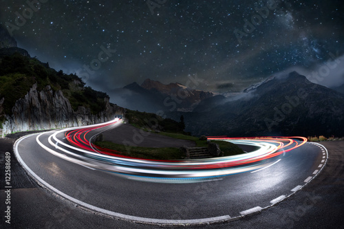 Papiers peints Alpes light trails on a hairpin bend and milky way in the background. swiss alps pass road at night, starry sky with galaxy and car light trails