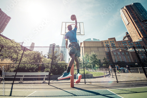 Photo  Street basketball athlete performing huge slam dunk on the court
