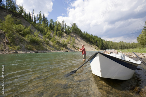 Young man fly fishing on the Elk River from a dory, Fernie, East Kootenays, British Columbia, Canada Poster