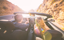 Couple Driving Fast On A Sport Convertible Car In The Canyons.